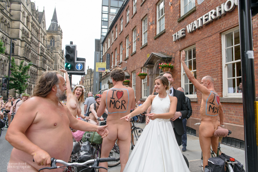 Bride and groom with the World Naked Bike Ride