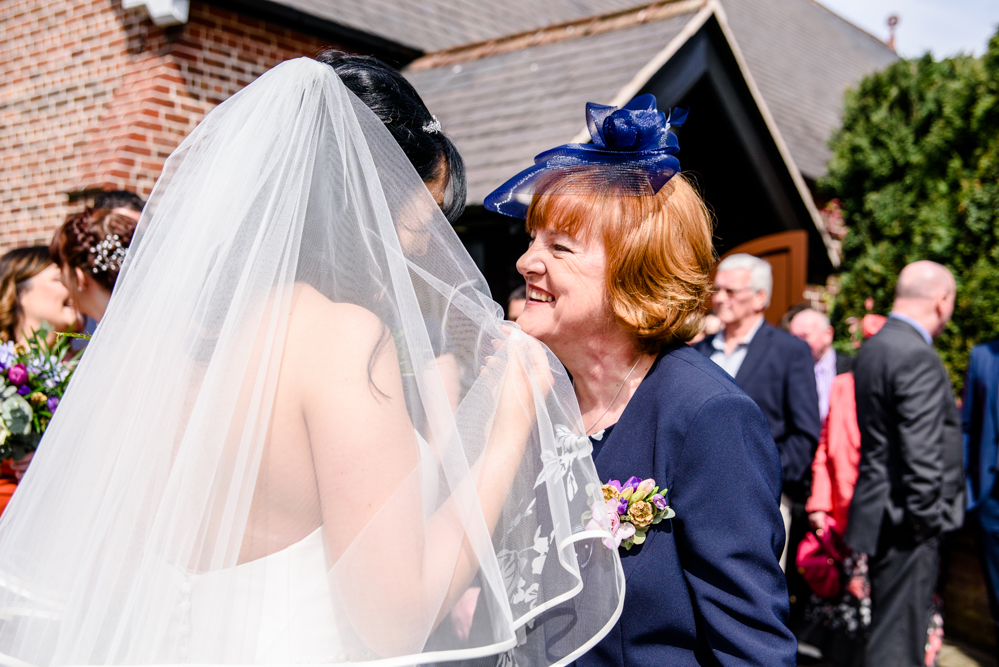 Guest congratulating the bride outside St Mary's Church in Middlewich