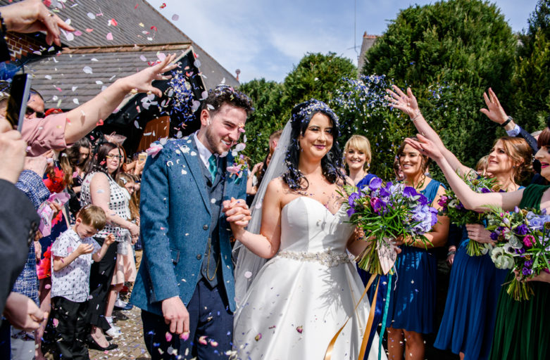 Bride and groom walking through confetti at St Mary's Church in Middlewich