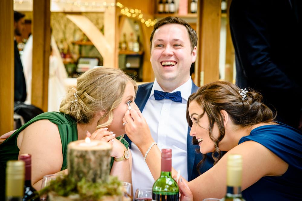 Bridesmaids touching up eye lashes at Oak Tree of Peover