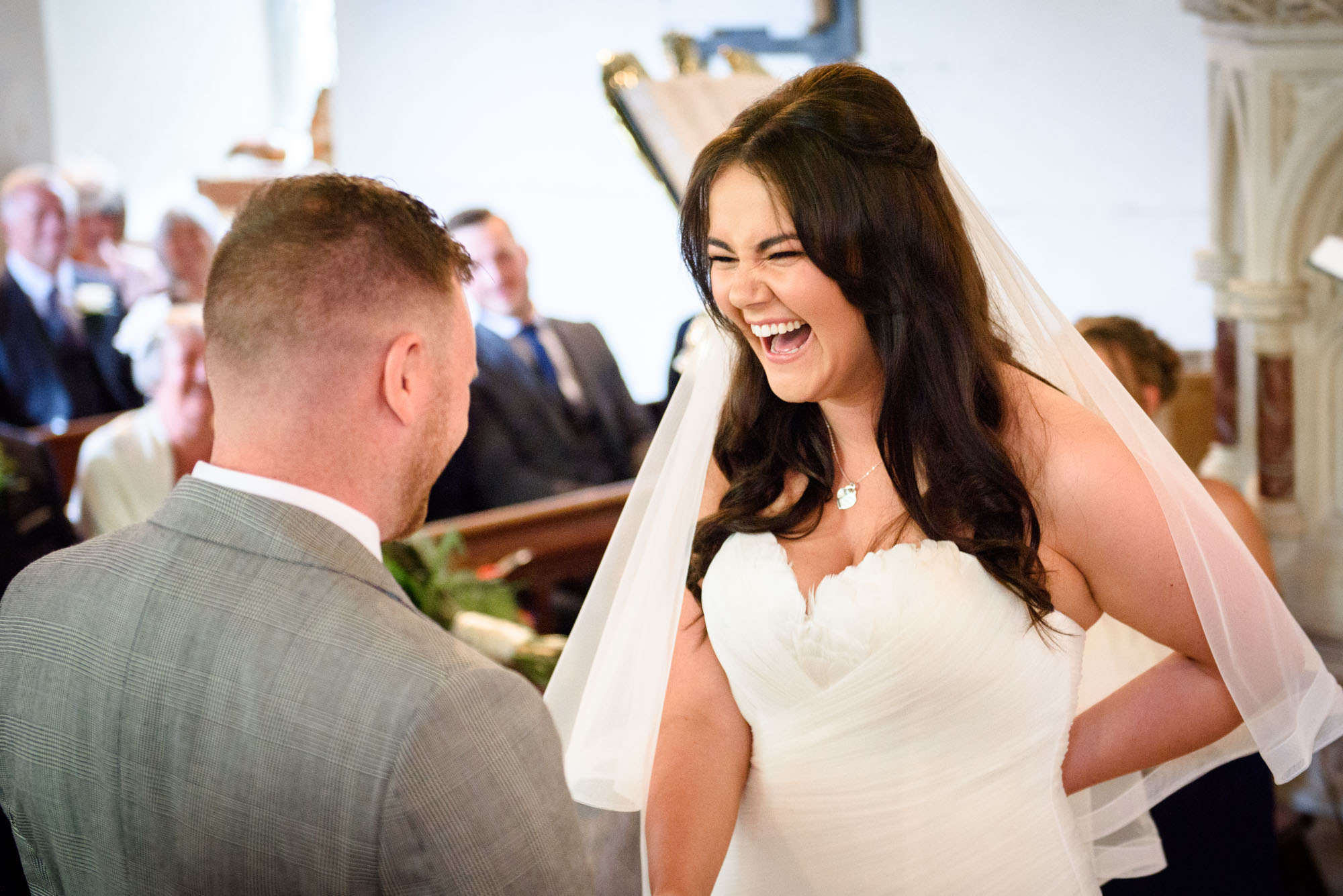 Bride laughing at st mary's church in Llanfairpwllgwyngyll