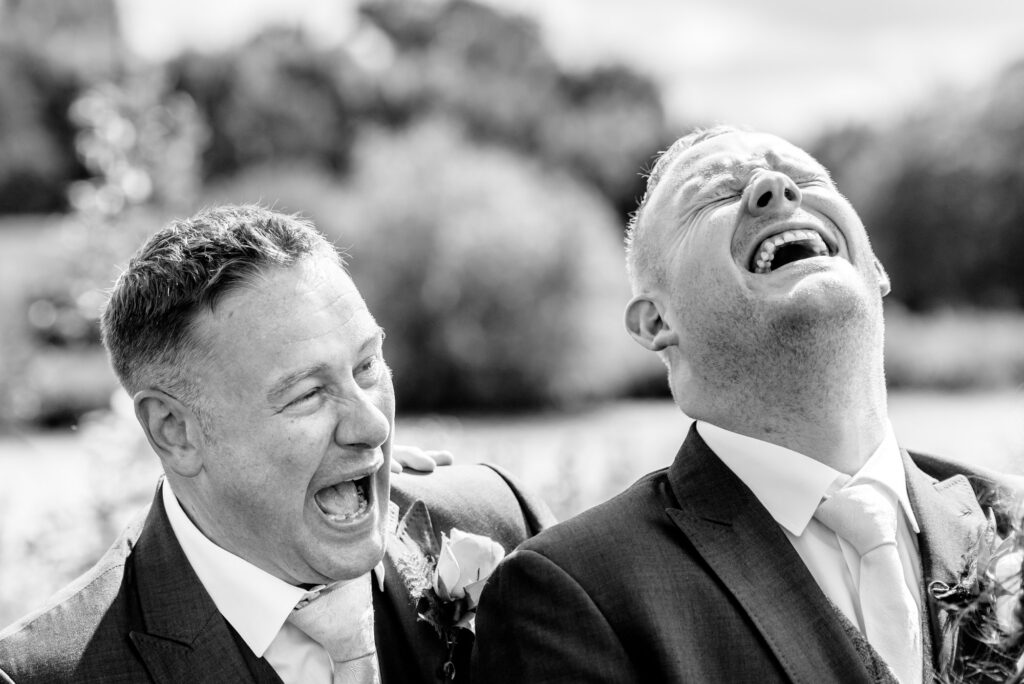 Groom and best man laughing their head off