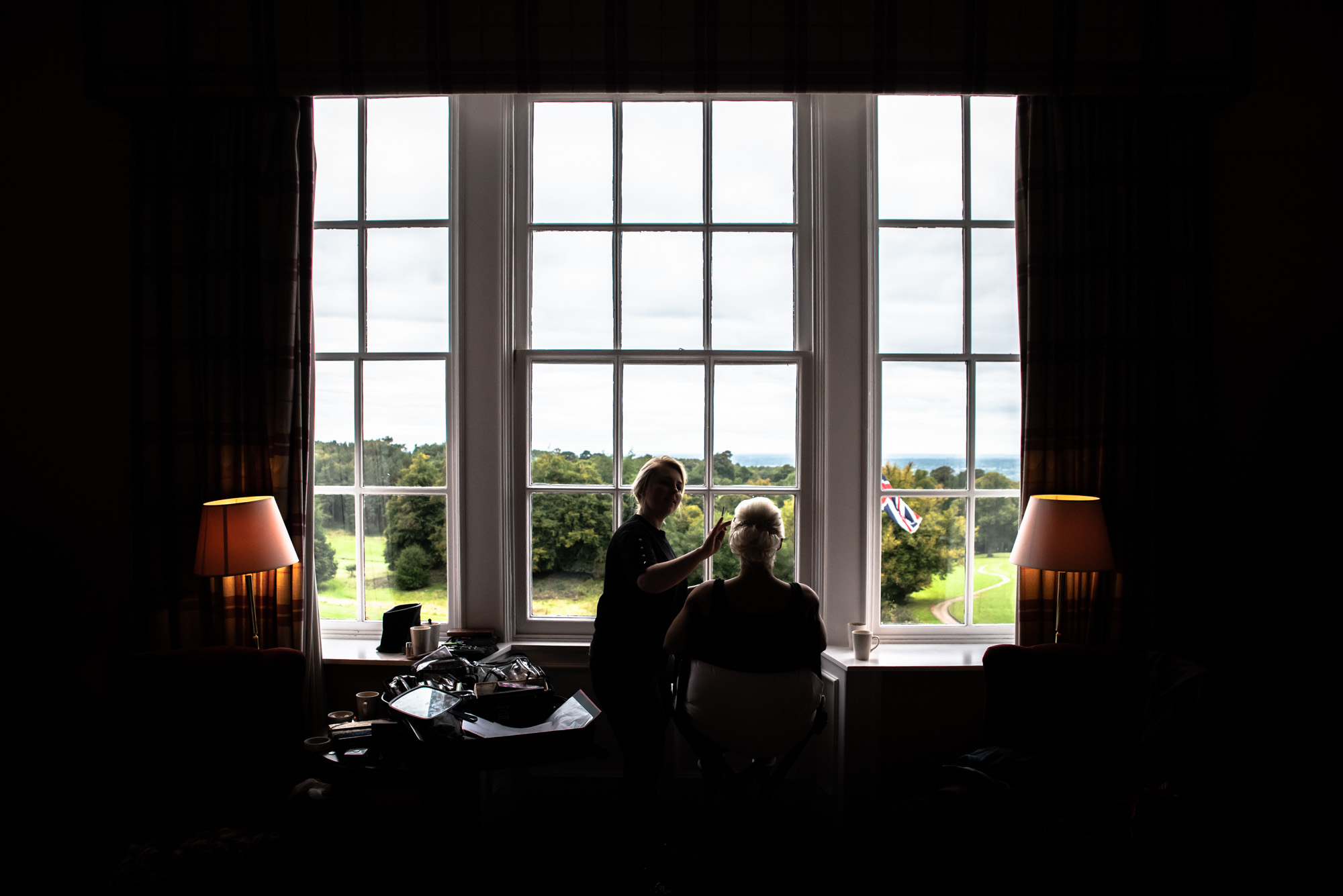Bride having makeup done in front of window at Shrigley Hall
