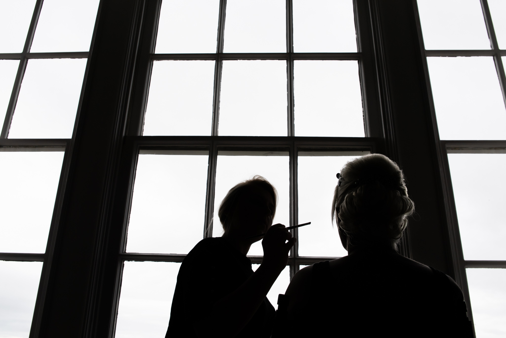 Bride silhouette having makeup done in front of window at Shrigley Hall