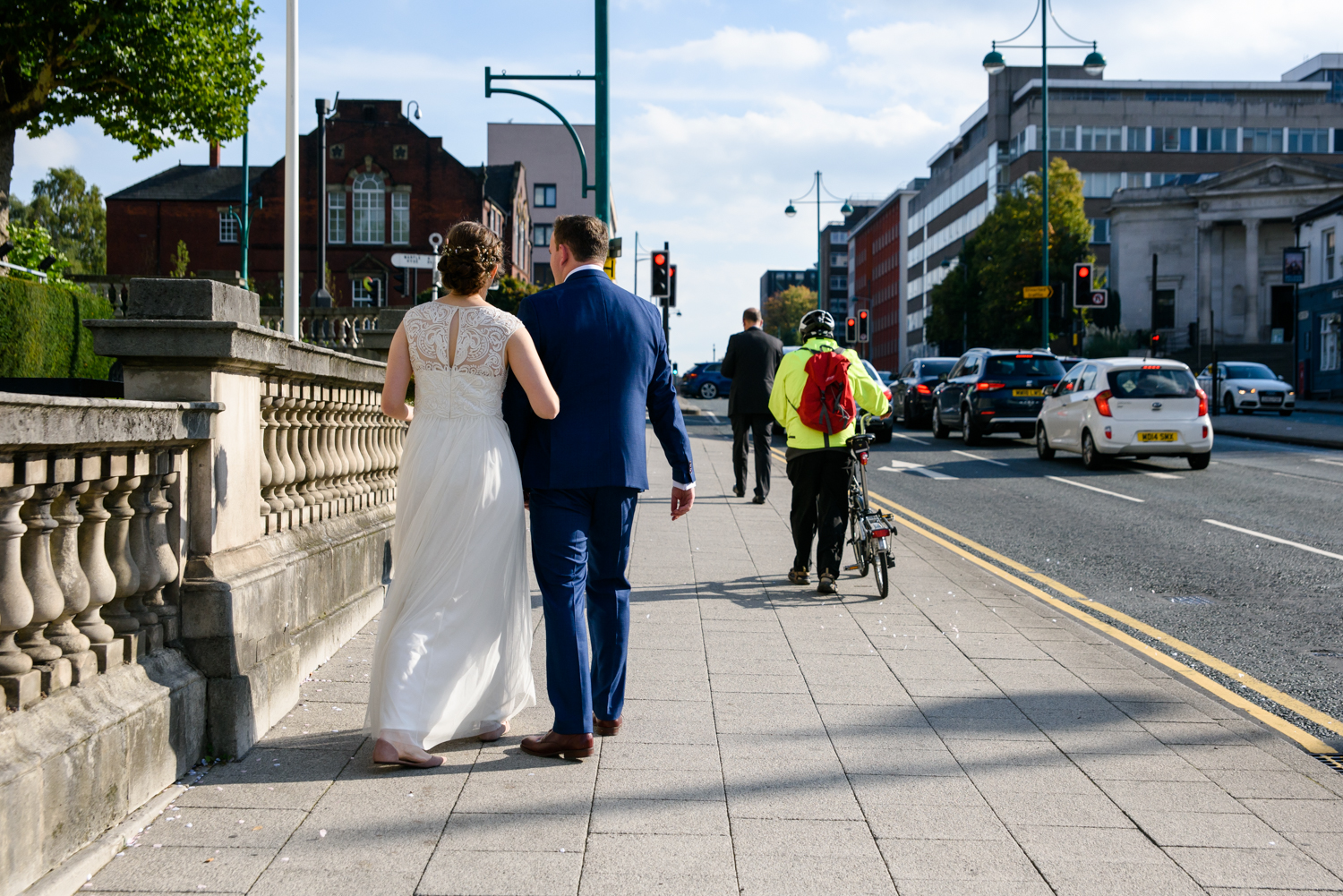 Bride and room walking down the A6 Stockport