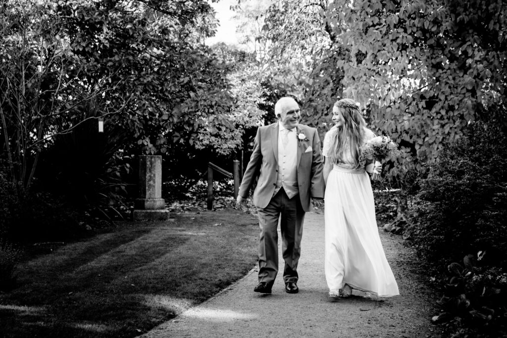 Dad walking with bride in Didsbury Parsonage gardens