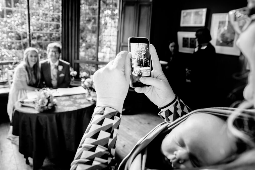 Mother with baby taking photo of the bride and groom