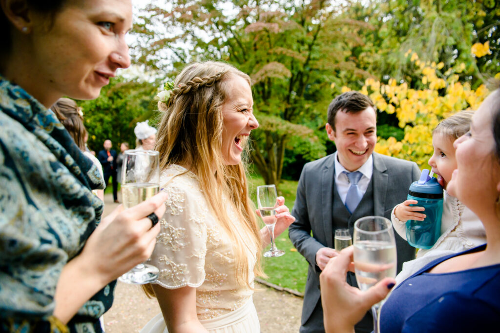 Bride laughing during the drink reception at Didsbury Parsonage
