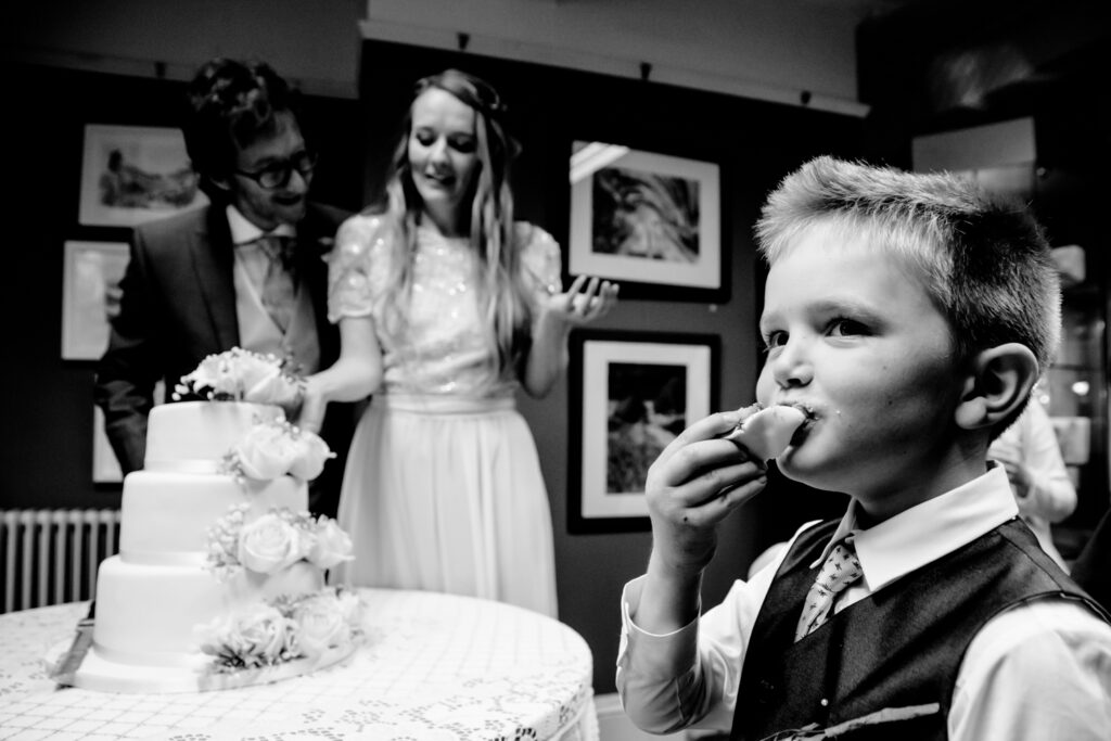 Boy stuffing his face whilst cutting the wedding cake